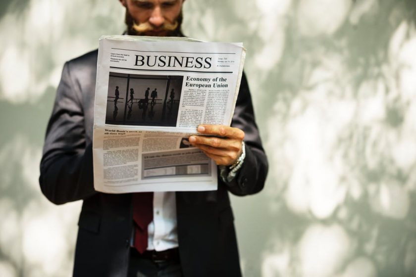 ビジネス新聞を読むスーツの男性