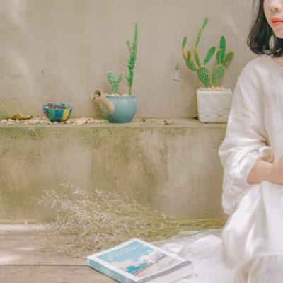 白い服を着て座る女性と本とサボテン