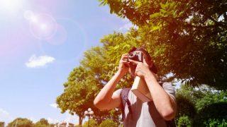 太陽と青い空にカメラを向ける海外の男性