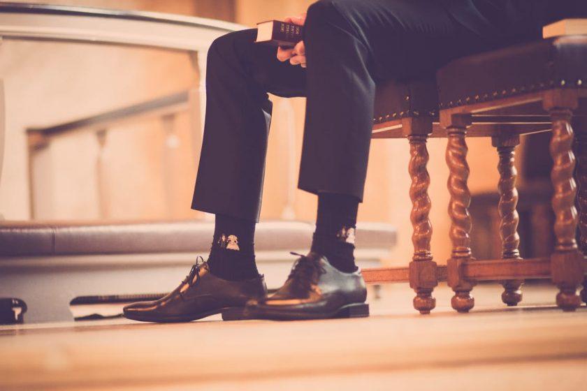 椅子に座るスーツの男性の足