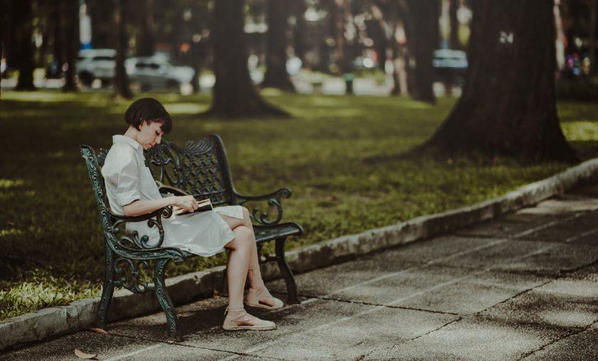 公園のベンチで本を読む綺麗な女性