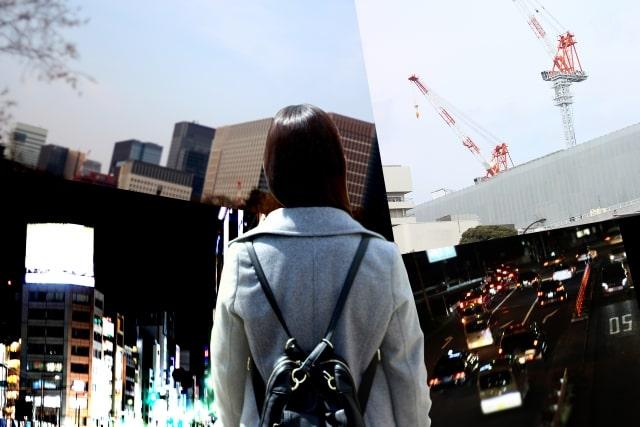 都会に立つ女性の後ろ姿