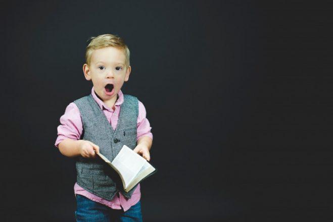本を開いて驚く金髪の少年