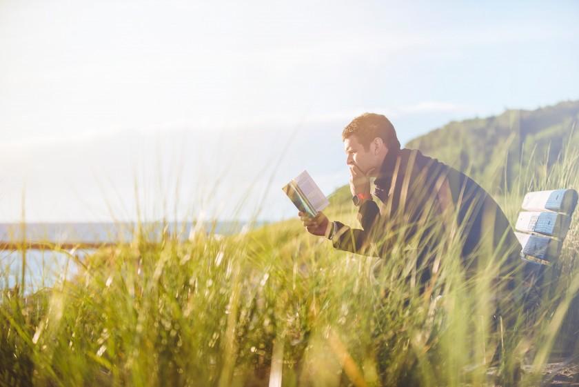外で読書をする外国人男性