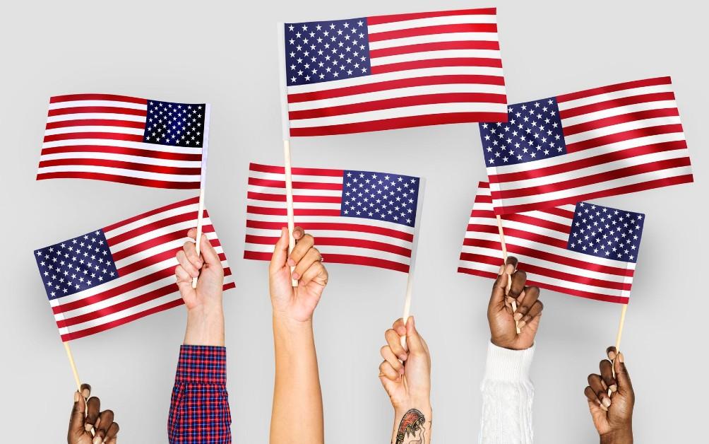 アメリカ国旗を持つ肌の色が違う複数の手