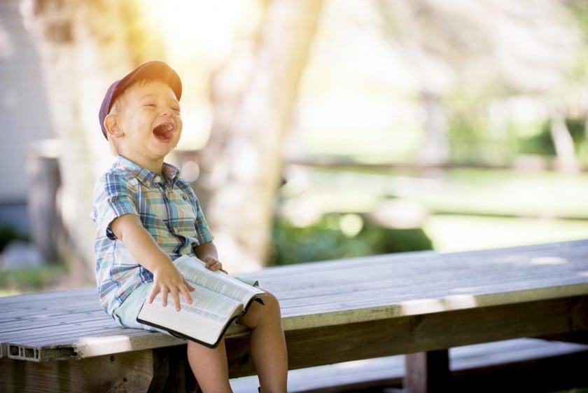 公園のベンチに座って満面の笑みを見せる外国人の少年
